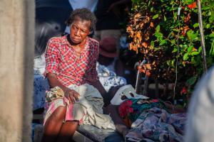 Une femme est assise dehors après le tremblement de terre de magnitude 7,2 qui a frappé Haïti le 14 août 2021 aux Cayes, en Haïti.
