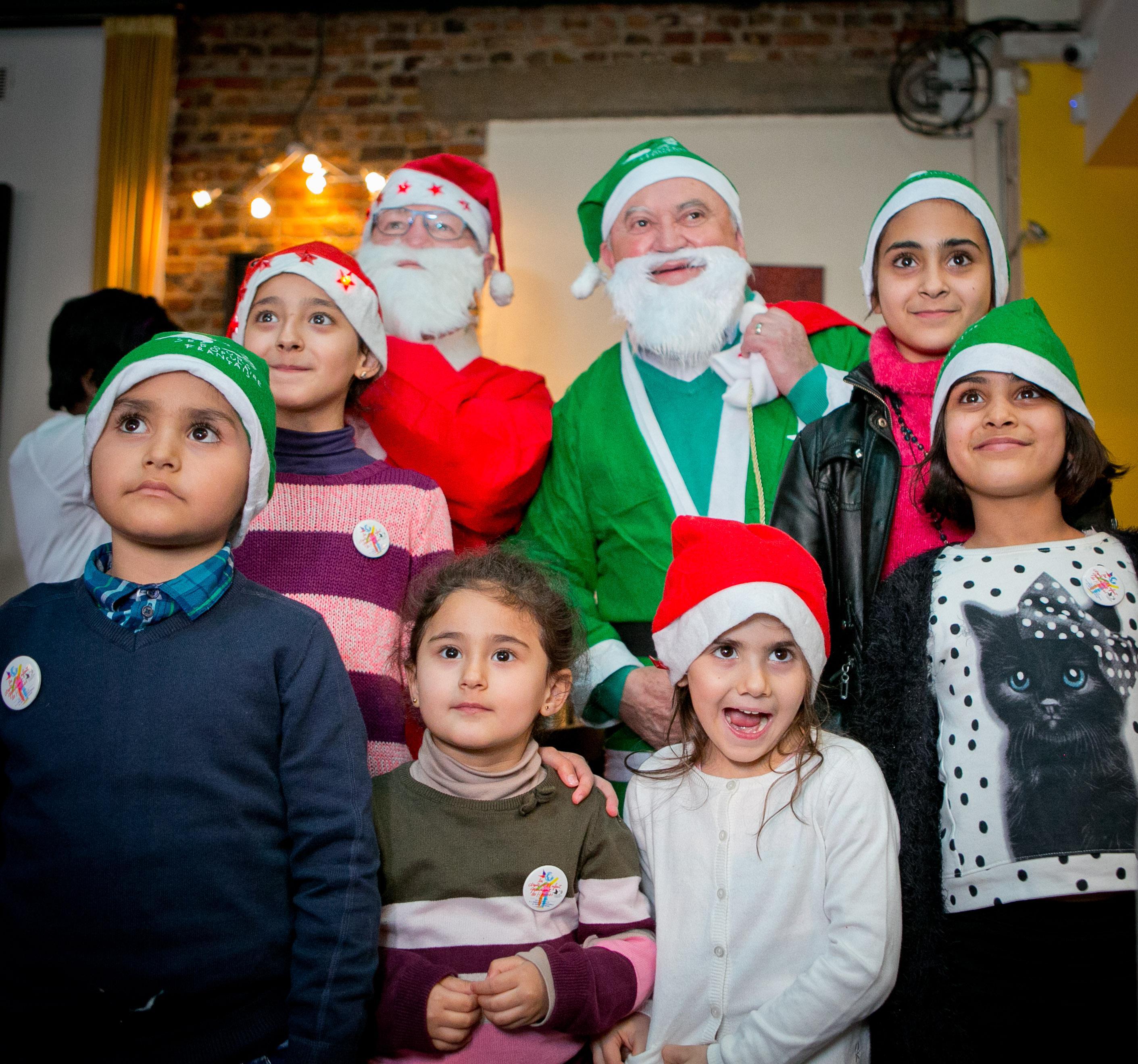 Les Pères Noël verts répondent toujours présents. Ici, un réveillon avec des enfants réfugiés venant de Syrie et d'Irak. Image d'archive de Noël 2015.