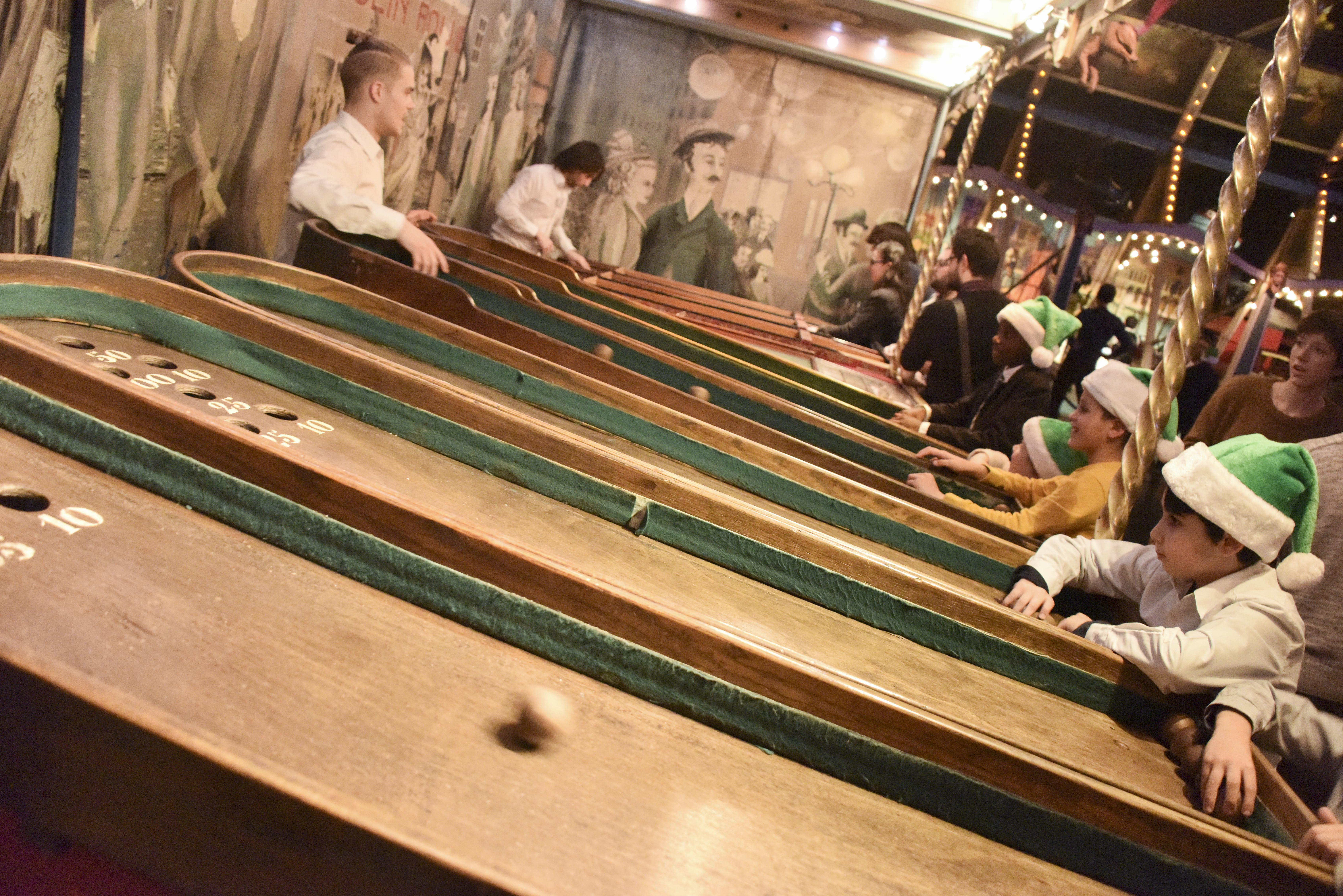 Les copains du monde jouent à la course des garçons de café au Musée des arts forains, au centre de Paris.