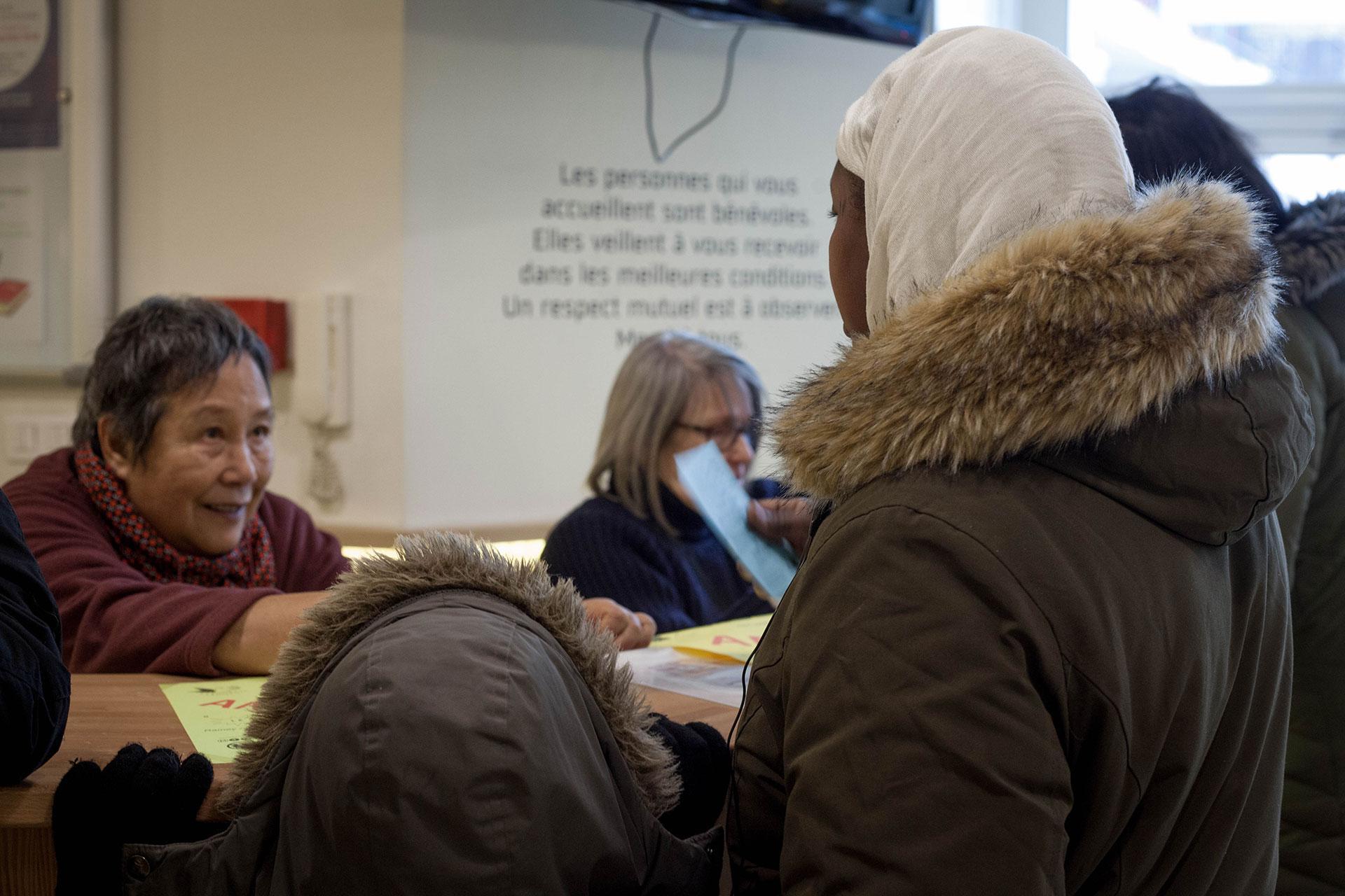 A l'accueil, Louise, bénévole au SPF de Paris, renseigne une maman accompagnée de son enfant.